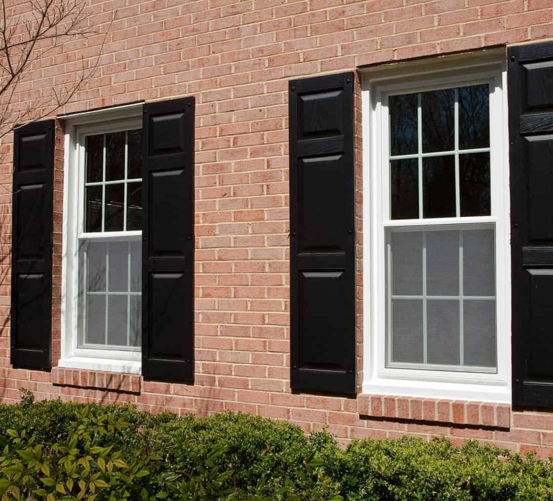 two double hung windows in a brick wall with black shutters