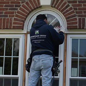 Thompson Creek worker installing window on brick house