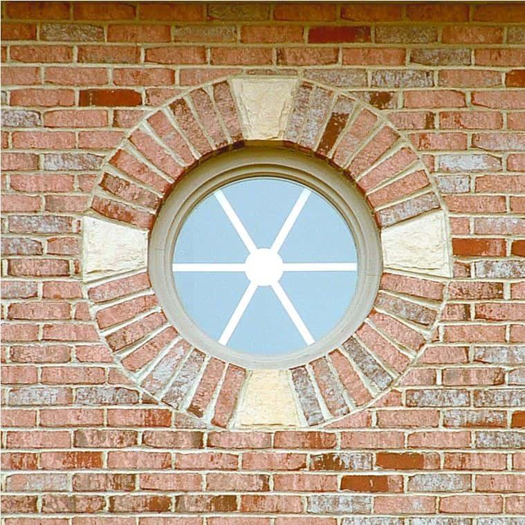 Round custom window on brick wall