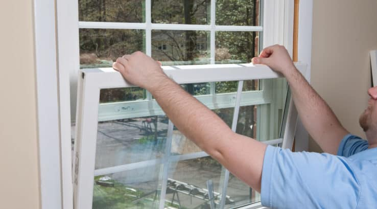 Man hanging double hung windowin frame