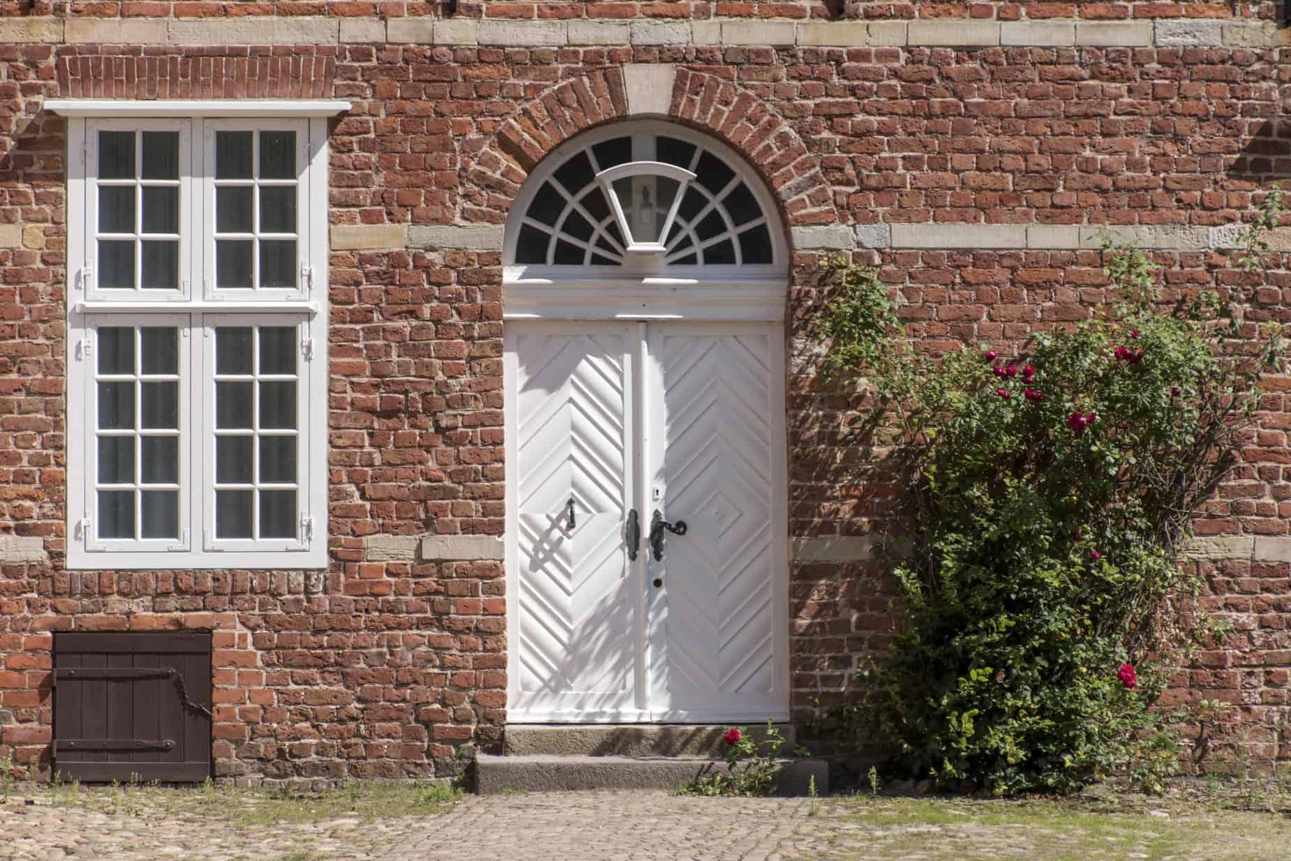 Transom window above white entrance of historic brick building