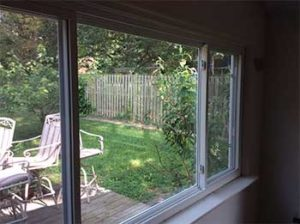 Large three lite slider window with view into backyard