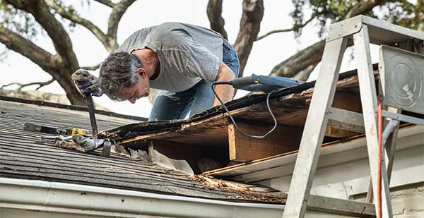 Man fixing leaking roof