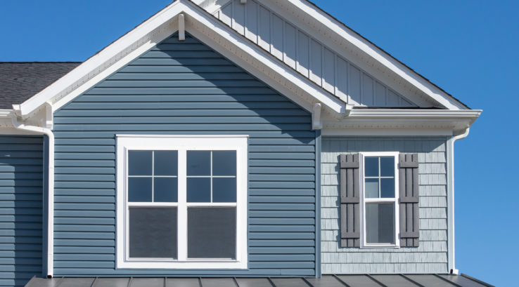 painting siding of a house