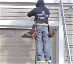 Thompson Creek worker installing vinyl siding on home