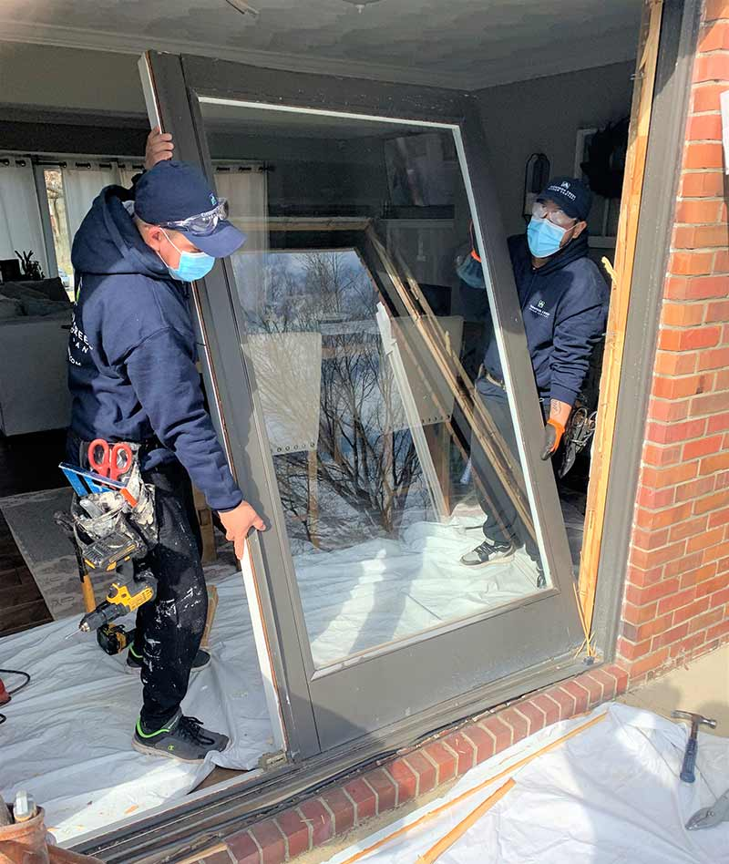 Thompson creek replacement sliding door being installed by two workers
